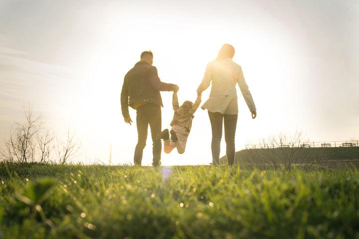 原っぱを歩く家族