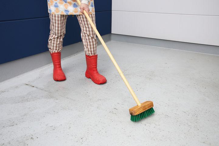 デッキブラシで掃除をする女性