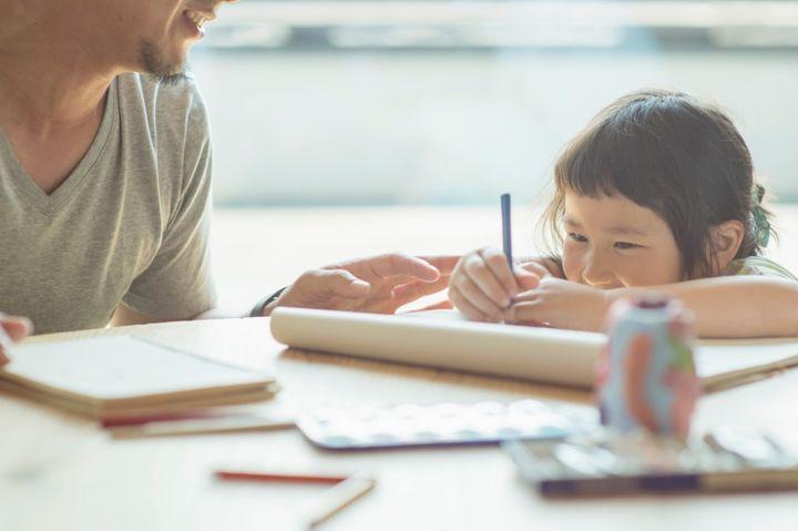 こたつで勉強する親子