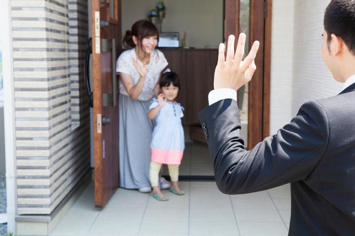 玄関でパパを見送るママと子ども