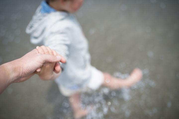 海で手を繋ぐ親子