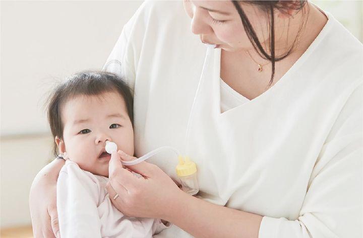 赤ちゃんの鼻水を吸うママ