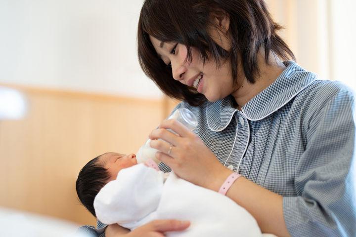 赤ちゃんにミルクをあげるママ