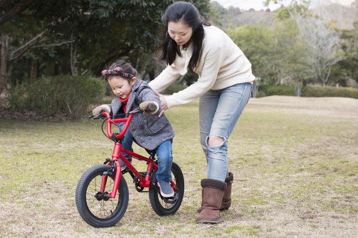 自転車を練習する子どもとママ