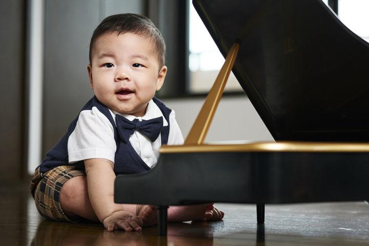 ピアノの前に座る赤ちゃん