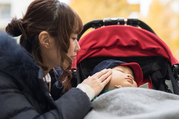 ベビーカーに乗る赤ちゃんを見るママ