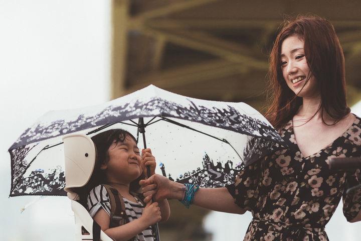 傘をさす子どもと持ってあげるママ
