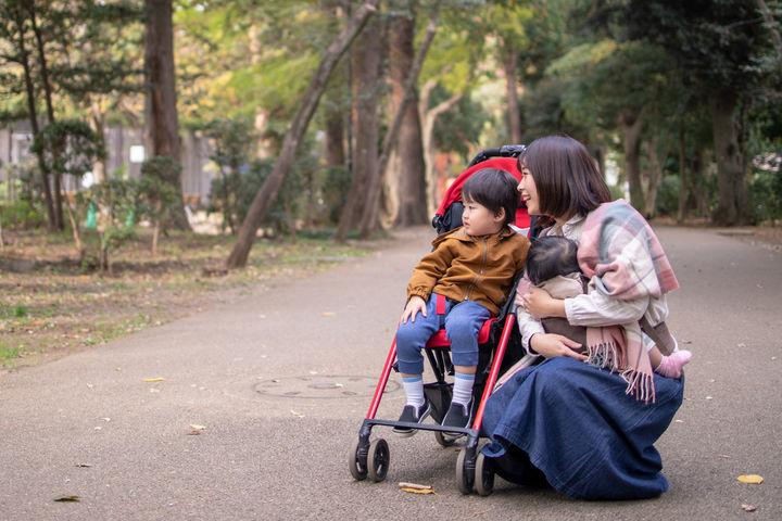 ベビーカーの子どもに寄り添うママ