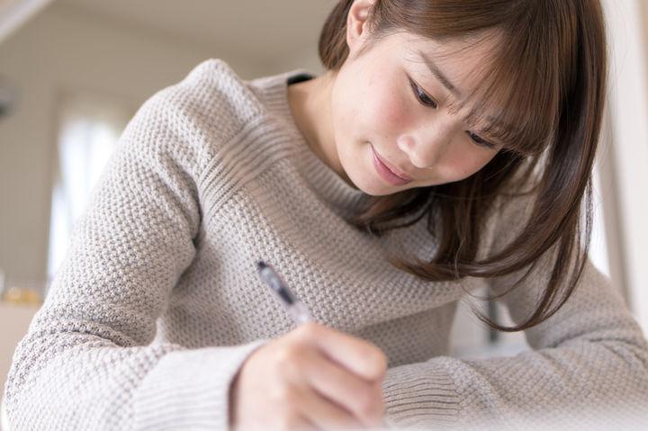 字を書く女性