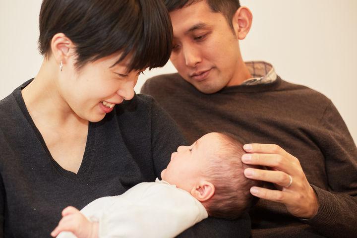赤ちゃんを見つめる夫婦