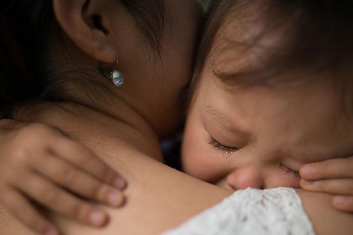 泣く子どもを抱きしめるママ