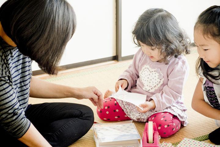 折り紙で遊ぶ親子