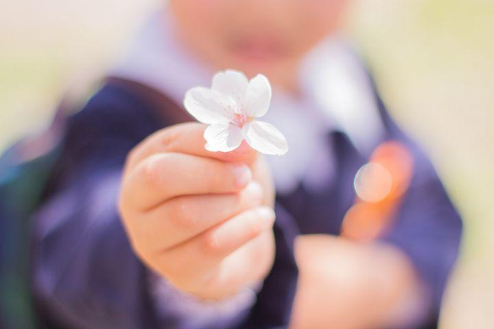 桜の花びらを持つ子ども