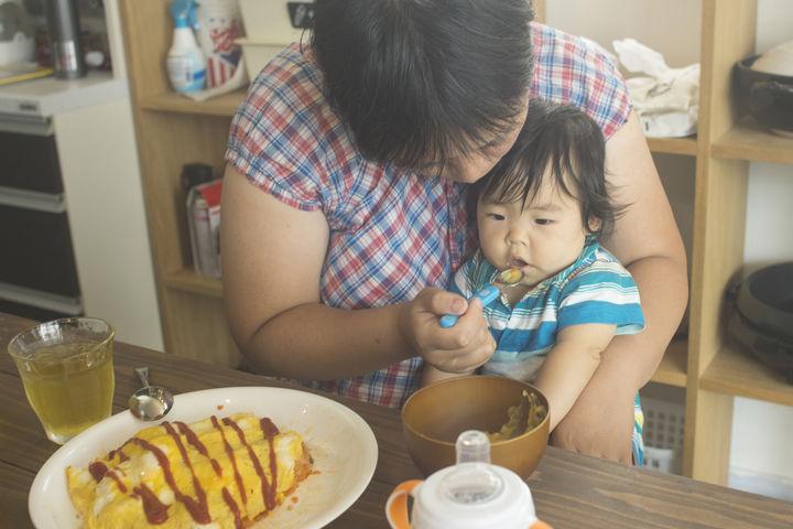 オムライスを食べさせてもらっている子供