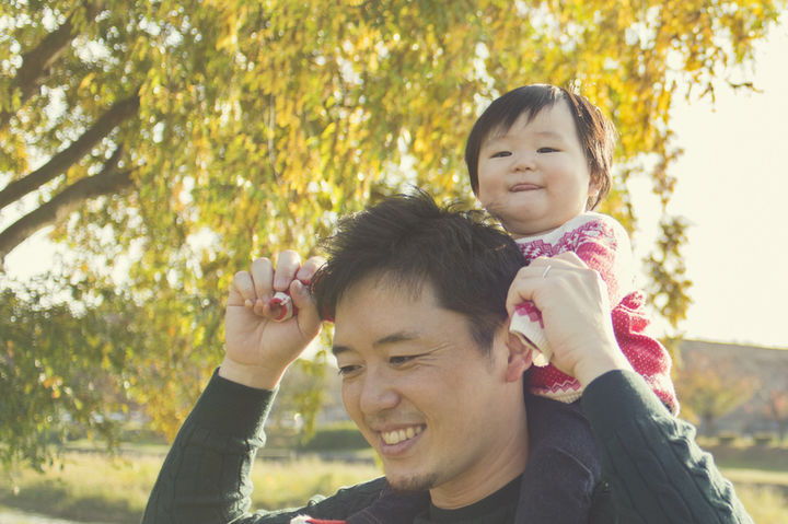 公園で赤ちゃんを肩車するパパ