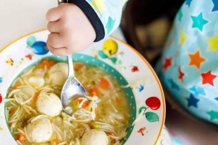 スプーンで離乳食を食べる赤ちゃんの手