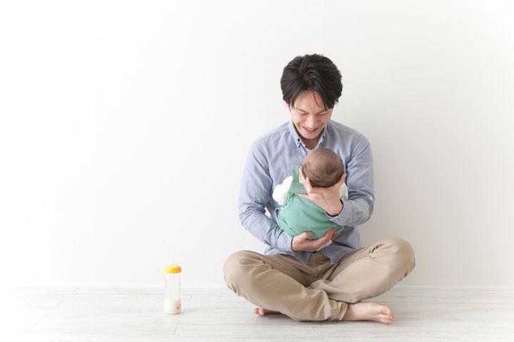 赤ちゃんにミルクを与えるパパ