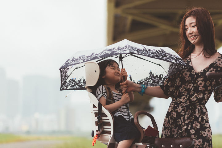 自転車に乗って傘をさす親子