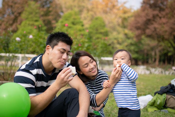 公園でサンドイッチを食べる親子
