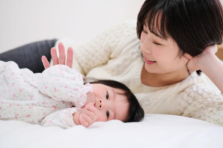 布団で寝転ぶママと赤ちゃん