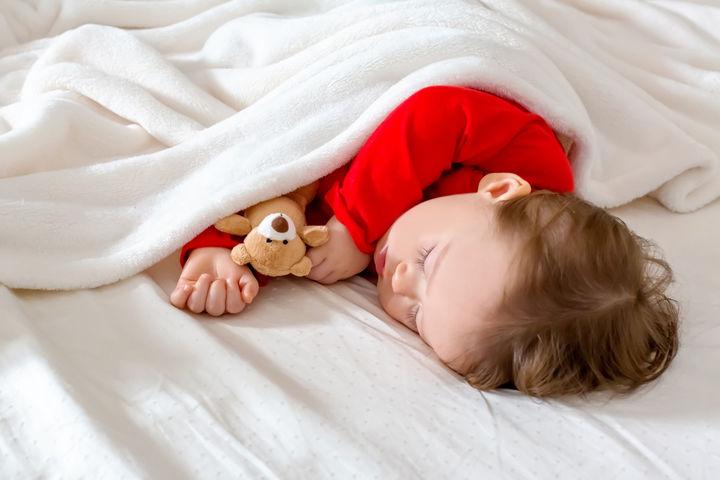 毛布で眠る赤ちゃん
