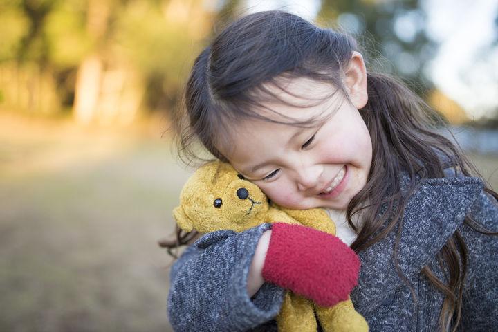 笑顔でぬいぐるみを抱く女の子