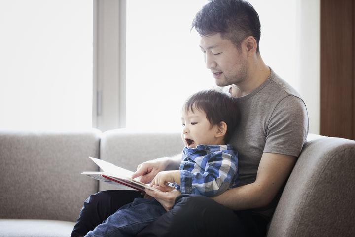 子供に絵本を読むパパ
