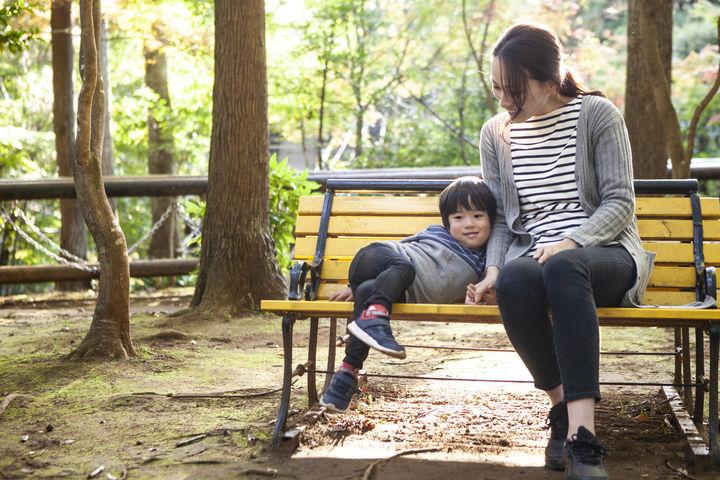 公園のベンチに座る男の子とママ
